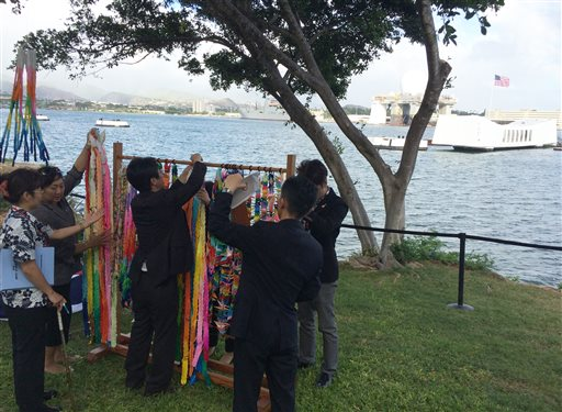 People hang paper cranes folded for peace near a memorial to the sunken battleship USS Arizona before a ceremony marking the 70th anniversary of the end of World War II, Friday, Aug. 15, 2015, in Pearl Harbor, Hawaii. Mayors and city council members from Honolulu and Nagaoka, Japan, joined the U.S. Pacific Fleet commander to lay wreaths and unveil a new plaque. (AP Photo/Audrey McAvoy)