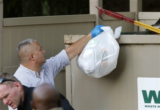 Investigators search garbage from a dumpster near the apartment of Vester Lee Flanagan II in Roanoke, Va., Wednesday, Aug. 26, 2015.  Flanagan filmed himself gunning down a WDBJ-TV reporter and cameraman during a live broadcast Wednesday and posted the video on social media after fleeing the scene.  (AP Photo/Steve Helber)