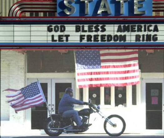 A biker rides by the State Theater in Falls Church, Va., a few days after 9/11. His flag helps tell the story of that tragic day. (Doug Thompson)
