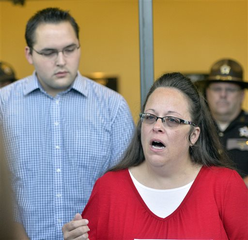 Rowan County Clerk Kim Davis, right, with her son Nathan Davis at her side, makes a statement to the media at the front door of the Rowan County Judicial Center in Morehead, Ky., Monday, Sept. 14, 2015. Davis announced that her office will issue marriage licenses under order of a federal judge, but they will not have her name or office listed. (AP Photo/Timothy D. Easley)
