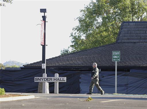 A Douglas County Sheriff's deputy walks past Snyder Hall at Umpqua Community College, Sunday, Oct. 4, 2015, in Roseburg, Ore. Armed with multiple guns, suspect Chris Harper-Mercer walked into a class at Snyder Hall on Thursday, killing nine and wounding several others before taking his own life. (AP Photo/Rich Pedroncelli)