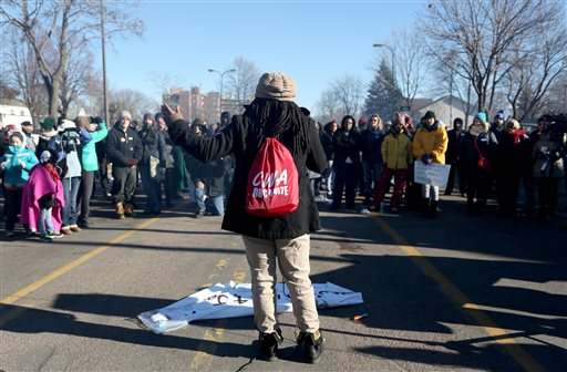 Alanna Galloway speaks to a crowd in front of a police precinct Saturday, Nov. 21, 2015, in Minneapolis.  An encampment of protesters outside a Minneapolis police station vowed Saturday to maintain their vigil over the death of a black man who was shot by police, saying they won't move until video recordings of the encounter are released and authorities change how they interact with communities they serve. (Kyndell Harkness/Star Tribune via AP)  MANDATORY CREDIT; ST. PAUL PIONEER PRESS OUT; MAGS OUT; TWIN CITIES LOCAL TELEVISION OUT