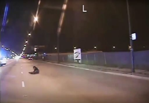 In this Oct. 20, 2014 frame from dash-cam video provided by Chicago Police Department, Laquan McDonald falls to the ground after being shot by officer Jason Van Dyke in Chicago. Van Dyke, who shot McDonald 16 times, was charged with first-degree murder Tuesday, Nov. 24, 2015. (Chicago Police Department via AP)