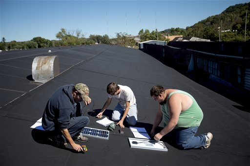 Glen Wilson, from left, Jeremy Smith and James Likens learn solar panel installation on the roof of the Coalfield Development Corp. during a class on Monday, Oct. 5, 2015, in Huntington, W.Va. Miners won't disappear completely from from coal country, despite the region's dark future. The coal they mine is high-quality stuff, used for making steel, not electricity. It may even be used to build the frames for solar panels that the students have learned to install, and that could further reduce demand for coal used for electricity. (AP Photo/David Goldman)