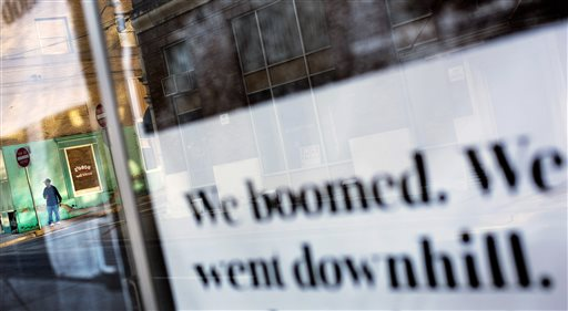 A pedestrian stands on a street corner as a message is displayed in a storefront window along the business district, Wednesday, Oct. 7, 2015, in Welch, W.Va. West Virginia is the only state in the country where more than half of adults are not working, according to the Census Bureau. It is tied with Kentucky for the highest percentage of residents collecting disability payments from Social Security, according to the Kaiser Family Foundation. And the death rate among working-age adults is highest in the nation, 55 percent higher the national average, according to the Centers for Disease Control and Prevention. (AP Photo/David Goldman)