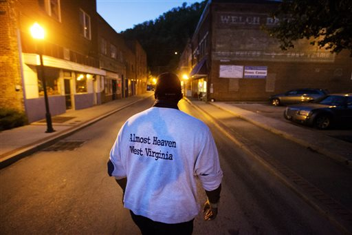 """Garnet Edwards Jr. walks on a street while volunteering for a nonprofit community organization in the business district on Monday, Oct. 5, 2015, in Welch, W.Va. """"There's no place like home. We're always going to be here,"""" said Edwards, a native of Welch. """"All it takes is one person to keep caring."""" (AP Photo/David Goldman)"""