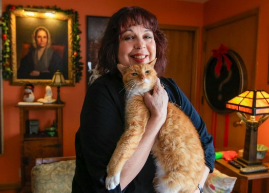 Graphic designer Rayna Collins poses for a  photo in her home in Lincoln, Neb., Friday, Dec. 11, 2015. Rising premiums and shaken faith among insurers have cast a cloud over sign-up season for President Barack Obama's health care law, and now it's crunch time again. Collins switched insurers for 2016 because the company she was with exited the market. Her premium will be just about the same, after subsidies the law provides for private coverage. But her deductible is going from $500 to $2600. (AP Photo/Nati Harnik)