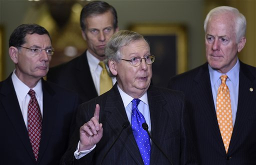 Senate Majority Leader Mitch McConnell of Ky., center, accompanied by, from left, Sen. John Barrasso, R-Wyo., Sen. John Thune, R-S.D., and Senate Majority Whip John Cornyn of Texas, speaks during a news  conference on Capitol Hill in Washington, Tuesday, Dec. 15, 2015, to discuss budget negotiations. (AP Photo/Susan Walsh)