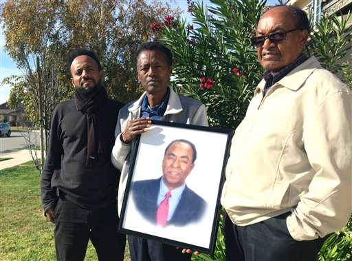 FILE - In this Dec. 5, 2015, file photo, family members of Isaac Amanios, from left, Robel Tekleab, Fessehatsion Gebreselassie and Abraham Amanios hold a portait of Isaac Amanios in Fontana, Calif. Isaac Amanios was killed during a Dec. 2, 2015 attack at his work holiday party at a social services center in San Bernardino, Calif. When Obama lands in Southern California Friday, Dec. 18, before heading to Hawaii for his annual Christmas vacation, he will encounter a group of families still burying their dead. Some are just beginning to grapple with what happened while others describe being in a state of continued shock. (AP Photo/Christine Armario, File)