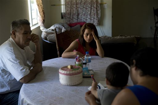 FILE - In this June 8, 2015, file photo, 18-year-old Dunia Bueso, center, and her relative, Augustin Vargas, left, look at Bueso's 1-year-old son, Joshua Tinoco, foreground, sitting on the lap of Martina Perez, at their home in Los Angeles. At a brief hearing, a government lawyer told the teenage mother that her son is an immigration enforcement priority for the United States and should be sent back to his native Honduras even though she is being allowed to stay and seek a green card. Only two states say their National Guard operations could provide facilities to house unaccompanied immigrant children following a request for options from the government. Most states say they aren't set up to handle that kind of housing or they lack the facilities. (AP Photo/Jae C. Hong, File)