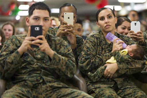 A group of Marines look on as President Barack Obama speaks during an event to thank service members and their families at Marine Corps Base Hawaii in Kaneohe Bay, Hawaii on Friday, Dec. 25, 2015. (AP Photo/Evan Vucci)