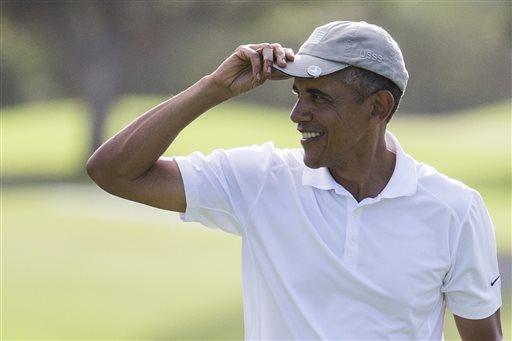 President Barack Obama tips his hat to the crowd after finishing a round of golf at Mid-Pacific Country Club during his family vacation on Monday, Dec. 28, 2015, in Kailua, Hawaii. (AP Photo/Evan Vucci)