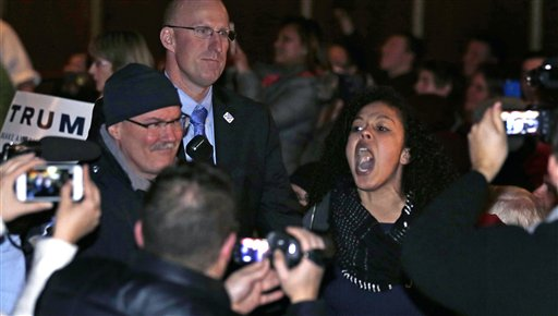 A protestor yells as she is escorted by security out of the audience during an address by Republican presidential candidate Donald Trump at a campaign stop at the Flynn Center of the Performing Arts in Burlington, Vt., Thursday, Jan. 7, 2016. (AP Photo/Charles Krupa)