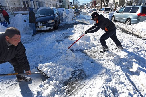 Angelo Delacrus, 15, right, of Passaic, who came from Dominican Republic recently, shovels snow in the middle of Van Buren Street in Passaic, N.J., Sunday, Jan. 24, 2016. (Kevin R. Wexler/The Record of Bergen County via AP) MANDATORY CREDIT