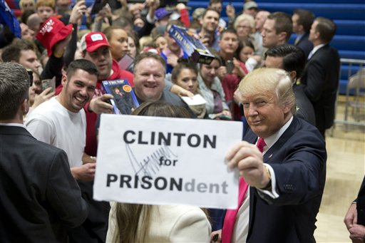 Republican presidential candidate Donald Trump pauses with a sign with his autograph on it while greeting his supporters at a rally Sunday, Jan. 31, 2016, in Council Bluffs, Iowa. (AP Photo/Jae C. Hong)
