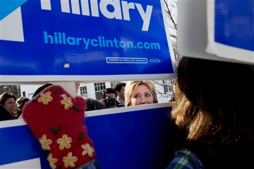 Democratic presidential candidate Hillary Clinton peeks through signs of hers as she greets supporters during a campaign stop in a Manchester, N.H., neighborhood Saturday Feb. 6, 2016. (AP Photo/Jacquelyn Martin)