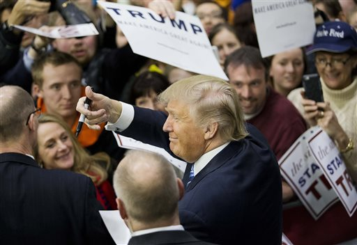 Republican presidential candidate Donald Trump gestures to the crowd as he signs autographs at a campaign event at Plymouth State University Sunday, Feb. 7, 2016, in Plymouth, N.H. (AP Photo/David Goldman)