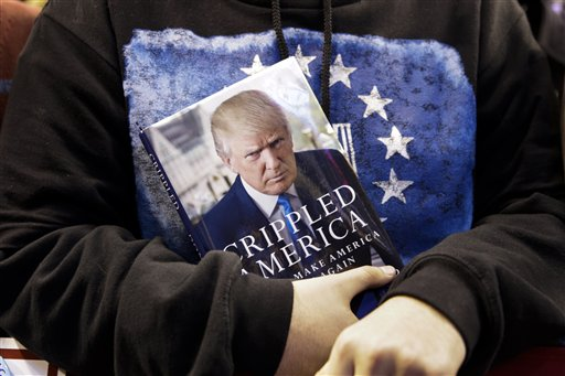 A supporter holds Republican presidential candidate, businessman Donald Trump's book during a campaign rally Monday, Feb. 8, 2016, in Manchester, N.H. (AP Photo/David Goldman)