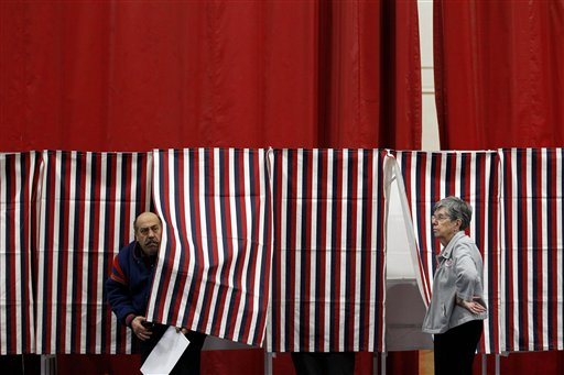 FILE - In this Jan. 10, 2012, file photo, ballot inspector Connie Bell, right, holds open a curtain on a voting booth during voting in the first-in-the-nation presidential primary at Memorial High School in Manchester, N.H. It's been 100 years since New Hampshire held its first presidential primary, and it seems like some of the current candidates have been hanging around for nearly that long.(AP Photo/Matt Rourke, File)