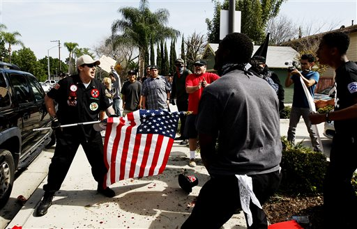 """A Ku Klux Klansman, left, uses an American flag to fend off angry counter protesters after members of the KKK tried to start a """"White Lives Matter"""" rally at Pearson Park in Anaheim, Calif., on Saturday, Feb. 27, 2016. The event quickly escalated into violence and at least two people had to be treated at the scene for stab wounds. (Luis Sinco/Los Angeles Times via AP)"""