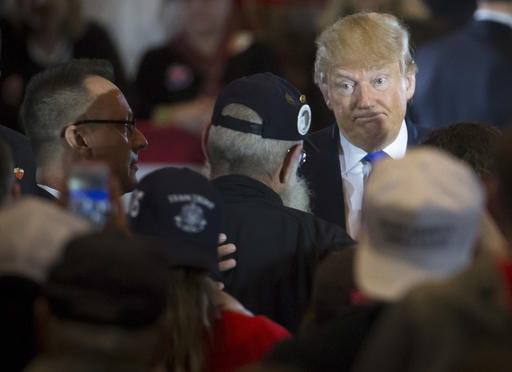"""Republican presidential candidate Donald Trump reacts as veteran Keith Moppin asks the candidate to clarify comments he made about Arizona Sen. John McCain during a campaign stop at the Savannah Center, Sunday, March 13, 2016, in West Chester, Ohio. Trump said in July while campaigning in Iowa that he dismissed the notion that McCain, the 2008 Republican nominee for president, was a hero """"Because he was captured."""" Trump said, """"I like people who weren't captured."""" (AP Photo/John Minchillo)"""