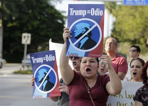"""Berta Sandes, 38, of Miami, an undocumented immigrant from Nicaragua, holds a sign which translates to """"Trump Equals Hate"""" during a protest against Republican presidential candidate Donald Trump outside of the Trump National Doral golf resort, Monday, March 14, 2016, in Doral, Fla. Voters go to the polls in Florida Tuesday for the primary election. (AP Photo/Lynne Sladky)"""