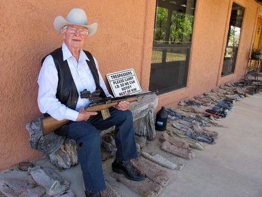 In this Tuesday, March 15, 2016 photo, Jim Chilton poses for a photo on the front porch of his home on his 50,000 acre ranch along the U.S-Mexico border in Arivaca, Ariz. Donald Trump's ambitious plan to build a giant wall on the border with Mexico is stirring up a range of emotions among voters who live there with some saying it would divide the two countries and others who say nothing short of a wall will fix the illegal immigration and drug smuggling problems. Chilton supports the wall and doesn't go anywhere on his ranch without his guns at the ready in case he encounters armed smugglers. (AP Photo/Brian Skoloff)