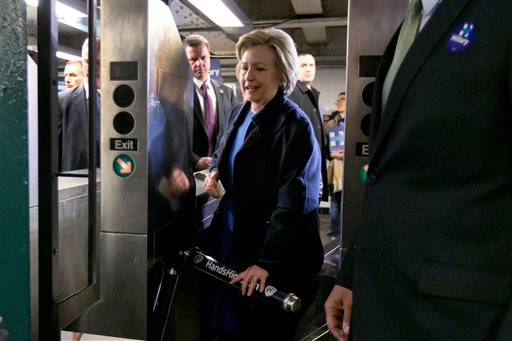 File-This April 7, 2016, file photo shows Democratic presidential candidate Hillary Clinton holding her Metrocard as she goes through the turnstile to enter the subway in the Bronx borough of New York. Competitive races have extended the primary calendars, requiring the candidates to have more local know-how. In New York City recently Ohio Gov. John Kasich took flack for eating pizza with a knife and fork. Clinton was mocked for struggling to use a Metrocard to ride the New York subway. And Bernie Sanders thought the subway still took tokens, which were phased out in 2003.  (AP Photo/Richard Drew)