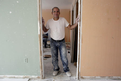 In this Monday, April 25, 2016 photo, Edgar Ospina, 50, poses for a photo where he is remodeling an apartment in Miami Beach, Fla. Ospina, who has spent almost half of his life in America after emigrating from his native Colombia, recently applied for naturalization. He was motivated to apply due to a possible Donald Trump presidency, in a year when immigration has taken center stage in the presidential campaign. (AP Photo/Lynne Sladky)