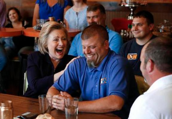 Democratic presidential candidate Hillary Clinton laughs with Scott Conley while talking to steelworkers in Ashland, Ky., Monday, May 2, 2016. (AP Photo/Paul Sancya)