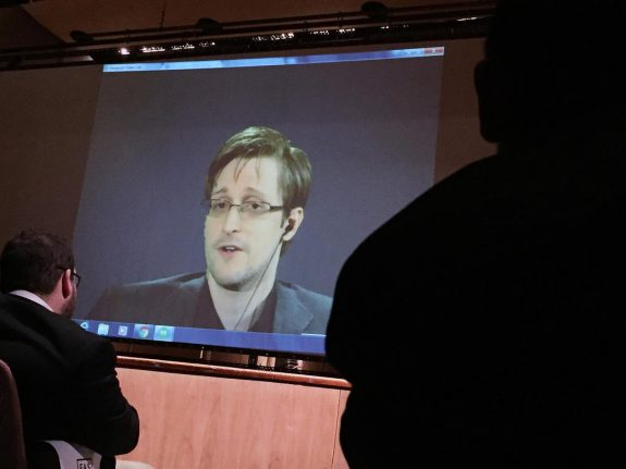 FILE- In this Feb. 17, 2016, file photo, former National Security Agency contractor Edward Snowden, center, speaks via video conference to people in the Johns Hopkins University auditorium in Baltimore. The Intercept, an online news site whose founding editors were the first to publish documents leaked by Snowden, released on Monday, May 16, the first batch of nine years' worth of the newsletters, which offer a behind-the-scenes glimpse into the NSA's work. (AP Photo/Juliet Linderman, File)