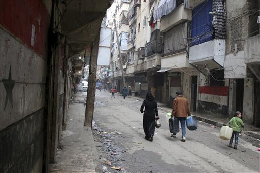 In this February 11, 2016, file photo, civilians walk with containers for fuel and water in Aleppo, Syria. Dozens of State Department employees have endorsed an internal document that advocates U.S. military action to pressure Syria's government into accepting a ceasefire and engaging in peace talks, officials said Thursday. The position is at odds with U.S. policy. (Alexander Kots/Komsomolskaya Pravda via AP, File)