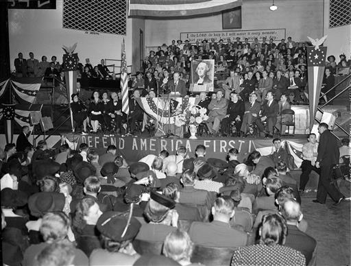 """This Oct. 3, 1941, file photo shows a crowd of over 4,000 people filled the Gospel Tabernacle in Fort Wayne, Ind., to hear Col. Charles Lindbergh, seen on the speaker's stand in the center, address a rally of the America First Committee. Presumptive Republican presidential nominee Donald Trump boils down his foreign policy agenda to two words: """"America First."""" For students of U.S. history, that slogan harkens back to the tumultuous presidential election of 1940, when hundreds of thousands of Americans joined the anti-war America First Committee. That isolationist group's primary goal was to keep the United States from joining Britain in the fight against Nazi Germany, which by then had overrun nearly all of Europe. But the committee is also remembered for the unvarnished anti-Semitism of some of its most prominent members and praise for the economic policies of Adolf Hitler. (AP Photo/File)"""
