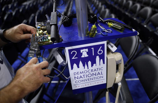 A worker wires a phone on the convention floor as setup continue before the 2016 Democratic Convention in Philadelphia, Saturday, July 23, 2016. (AP Photo/Carolyn Kaster)