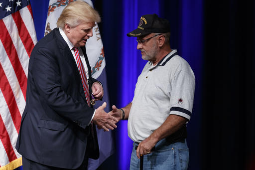 Republican presidential candidate Donald Trump shakes hands with Louis Dorfman, after Dorfman gave his Purple Heart medal to Trump during a campaign rally at Briar Woods High School, Tuesday, Aug. 2, 2016, in Ashburn, Va. (AP Photo/Evan Vucci)