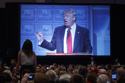 A demonstrator stands on a chair and yells as Republican presidential candidate Donald Trump delivers an economic policy speech to the Detroit Economic Club, Monday, Aug. 8, 2016, in Detroit. (AP Photo/Evan Vucci)