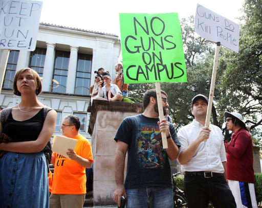 Students holds signs and sex toys as they protest a campus carry law in Austin, Texas, Wednesday Aug. 24, 2016. Hundreds of University of Texas students waved sex toys at a campus rally during the first day of classes, protesting a new state law that allows concealed handguns in college classrooms, buildings and dorms. (AP Photo/John Mone)