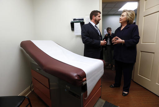 """FILE - In this May 2, 2016 file photo, Democratic presidential candidate Hillary Clinton listens to Dr. Christopher Beckett, CEO of Williamson Health and Wellness Center during a tour an exam room of the facility in Williamson, W.Va. With the hourglass running out for his administration, President Barack Obama's health care law is struggling in many parts of the country. Double-digit premium increases and exits by big-name insurers have caused some to wonder whether """"Obamacare"""" will go down as a failed experiment. (AP Photo/Paul Sancya)"""