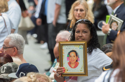 FILE- In this Sept. 11, 2015 file photo, a woman holds up a photograph during the ceremony commemorating the Sept. 11, 2001 terrorist attacks at the World Trade Center site in New York. Victims' relatives and dignitaries will once again convene Sunday, Sept. 11, 2016, on the memorial plaza at the World Trade Center for one of the constants in how America remembers 9/11 after 15 years, the anniversary ceremony itself. (AP Photo/Bryan R. Smith, File)