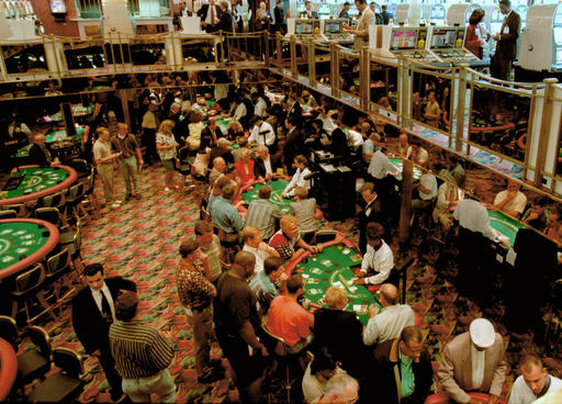 FILE - In this June 3, 1996, file photo, gamblers fill the tables on two decks during a practice cruise on the Majestic Star Casino in Gary, Ind. Donald Trump's appeal to black voters sounds familiar in Gary, and not in a good way. In 1993, Trump swooped into Gary on his private jet and pledged to make the down-on-its-luck city great again with a riverboat casino along a Lake Michigan shoreline littered with shuttered factories. Little more than a decade later Trump's company declared bankruptcy, leaving behind lawsuits and hard feelings in the majority-black city.(AP Photo/Michael Conroy, File)
