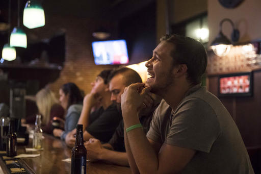 Roman Mitchell laughs as he watches the presidential debate between Democratic presidential nominee Hillary Clinton and Republican presidential nominee Donald Trump at Jefferson Social, Monday, Sept. 26, 2016, in downtown Cincinnati. (AP Photo/John Minchillo)
