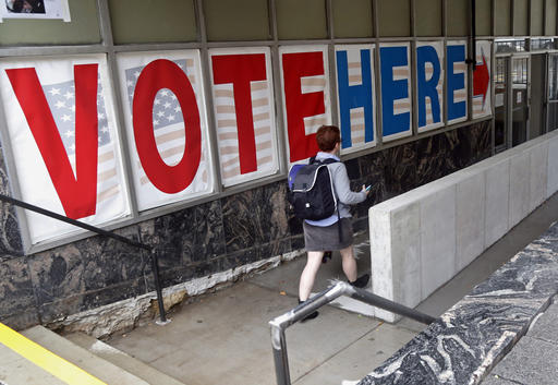 FILE - In this Sept. 23, 2016 file photo, a voter woman passes a large sign before voting in Minneapolis. More people are seeking or casting early ballots in the critical states of North Carolina and Florida than at this point in 2012, with Hillary Clinton the likely benefactor, as early voting shows signs of surging nationwide. (AP Photo/Jim Mone, File)