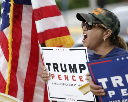 Cuban-born Lilia Morraz of Miami, demonstrates with other supporters of Republican presidential candidate Donald Trump outside a rally for Democratic presidential candidate Hillary Clinton, and former vice president Al Gore, Tuesday, Oct. 11, 2016, in Miami. During the event, Clinton will emphasizing her plans to develop more clean energy, reduce fossil fuel production and build more weather-resistant infrastructure. (AP Photo/Wilfredo Lee)