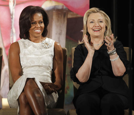 FILE - In this March 8, 2012, file photo, then-Secretary of State Hillary Clinton and first lady Michelle Obama attend the 2012 International Women of Courage Awards at the State Department in Washington. Clinton and Obama are slated to campaign together for the first time at a rally in Winston-Salem, North Carolina on Oct. 27, 2016. The event will bring together two women who are a study in contrasts. Clinton is perhaps one of the least traditional first ladies in modern history, while Obama has fully embraced tradition. (AP Photo/Charles Dharapak, File)