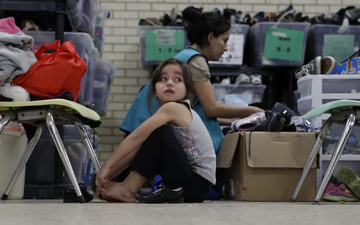 In this Sunday, Nov. 13, 2016, photo, a young migrants girl from Central American newly released after processing by the U.S. Customs and Border Patrol is fitted shoes at the Sacred Heart Community Center in the Rio Grande Valley border city of McAllen, Texas, Sunday, Nov. 13, 2016. (AP Photo/Eric Gay)
