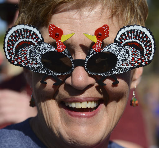 Vicki Tompkins wears turkey sunglasses to Pete's Thanksgiving Block Party on Thursday, Nov. 24, 2016, in Neptune Beach, Fla. People jammed First Street in front of Pete's Bar enjoying beverages and some wearing festive hats and outfits. (Bob Mack/The Florida Times-Union via AP)