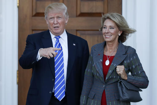 FILE - In this Nov. 19, 2016 file photo, President-elect Donald Trump and Betsy DeVos pose for photographs at Trump National Golf Club Bedminster clubhouse in Bedminster, N.J. Trump has chosen charter school advocate DeVos as Education Secretary in his administration. (AP Photo/Carolyn Kaster, File)