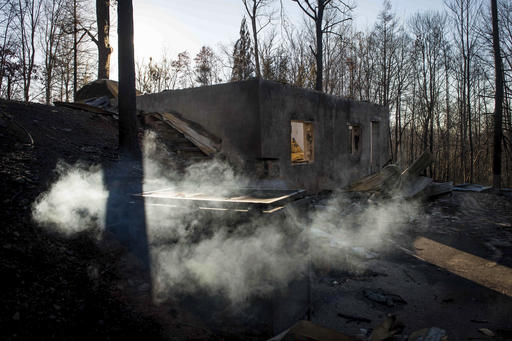 Smoke billows from the remains of a home on the northern outskirts of Gatlinburg, Tenn., Thursday, Dec. 1, 2016. A devastating wildfire destroyed numerous homes and buildings on Monday. (Andrew Nelles/The Tennessean via AP)