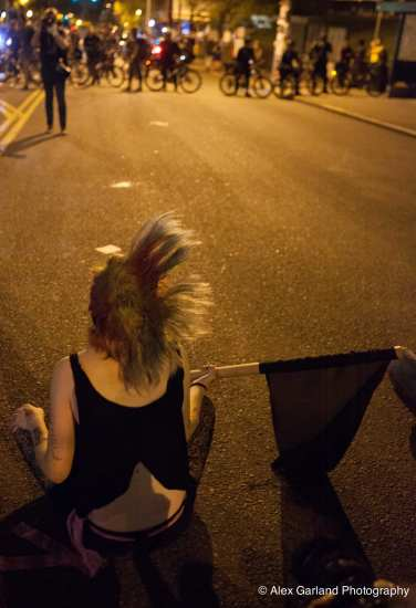 A protester sits in E Pine during May Day 2014 demonstrations on Capitol Hill (Image: CHS)