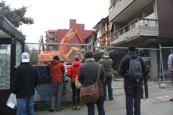 A small crowd watches the old Marion Apartments building come down at Pine and Bellevue in 2012